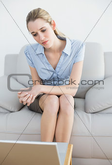 Thoughtful classy businesswoman sitting on couch looking at laptop