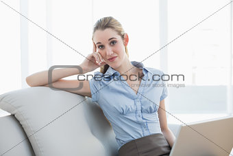 Smart businesswoman sitting on couch holding her notebook