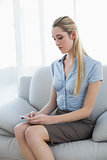 Serious beautiful businesswoman texting with her smartphone sitting on couch
