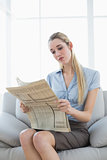Attractive calm businesswoman sitting on couch while reading newspaper
