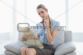 Thoughtful lovely businesswoman reading newspaper while sitting on couch