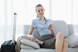 Attractive calm businesswoman using her smartphone while sitting on couch