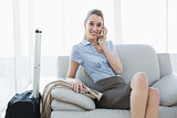 Gorgeous calm businesswoman phoning while sitting on couch