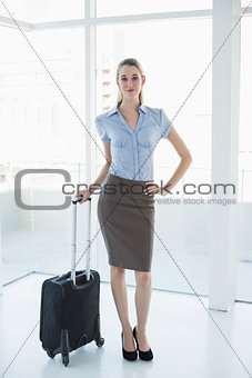 Attractive peaceful businesswoman posing holding a suitcase