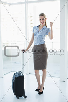 Beautiful happy businesswoman posing cheerfully standing in her office