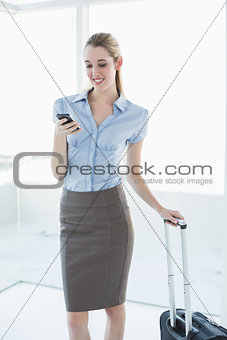 Beautiful content businesswoman using her smartphone standing in her office