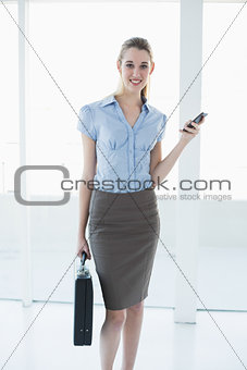 Calm content businesswoman holding her smartphone and briefcase