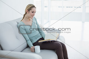 Attractive blonde woman relaxing reading a book holding a cup