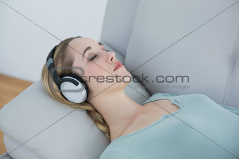 Casual blonde woman listening to music lying on couch