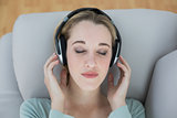 Pretty natural woman listening with headphones to music lying on couch
