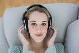 Beautiful casual woman listening with headphones to music lying on couch