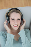 Gorgeous young woman listening with headphones to music smiling at camera