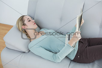 Slender natural woman reading newspaper lying on couch