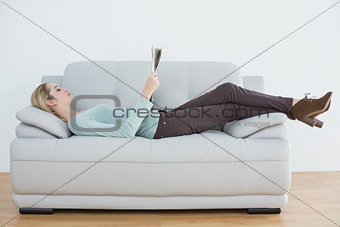 Attractive blonde woman reading newspaper lying on couch