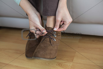Slender woman tying her shoelaces