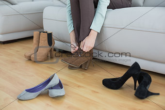 Slim woman tying her shoelaces sitting on couch