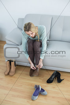 Attractive blonde woman tying her shoelaces sitting on couch