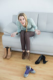 Cheerful casual woman tying her shoelaces sitting on couch
