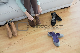 Slender young woman tying her shoelaces sitting on couch