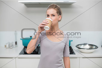 Calm gorgeous blonde drinking from disposable cup