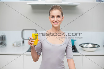 Cheerful gorgeous model looking at camera holding orange juice
