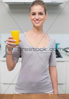 Smiling gorgeous model looking at camera holding orange juice