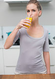Calm gorgeous model looking at camera drinking orange juice