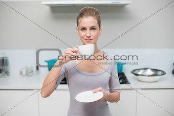 Happy gorgeous model looking at camera holding mug