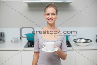Lucky gorgeous model looking at camera holding mug