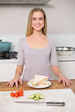Smiling gorgeous model standing behind plate with sandwich