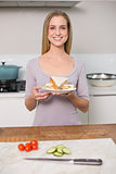 Smiling gorgeous model holding plate with sandwich