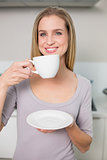 Smiling gorgeous model holding plate with cup