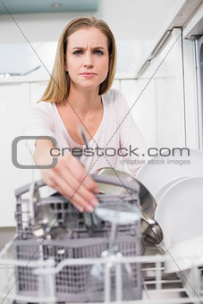 Frowning gorgeous model kneeling behind dish washer
