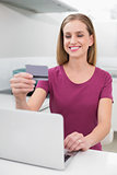 Smiling casual woman using laptop and credit card