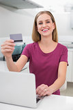 Cheerful casual woman using laptop and credit card