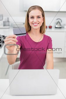 Blonde casual woman using laptop and credit card