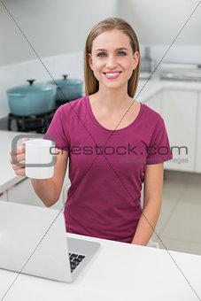Blonde casual woman using laptop holding mug