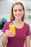 Happy casual woman holding glass of orange juice