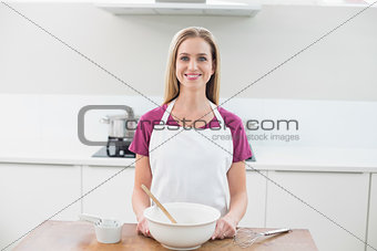 Casual smiling model standing behind baking utensils