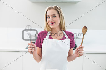 Casual cheerful blonde showing wooden spoon and whisk