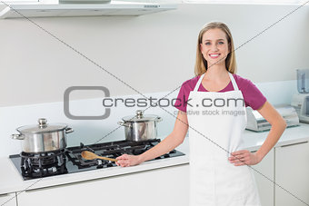 Casual happy blonde standing next to stove top