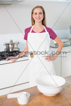 Casual content blonde standing next to stove