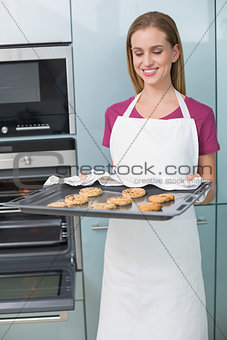 Casual cheerful woman holding baking tray with cookies