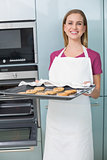 Casual laughing woman holding baking tray with cookies