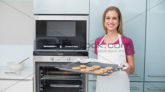Casual gleeful woman holding baking tray with cookies