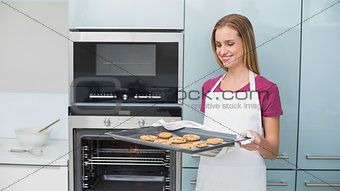 Casual blonde woman holding baking tray with cookies