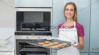 Casual content woman holding baking tray with cookies