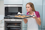 Casual attractive woman smelling baking tray with cookies