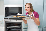 Casual laughing woman smelling baking tray with cookies