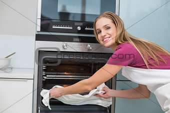 Casual happy woman taking baking tray out of oven